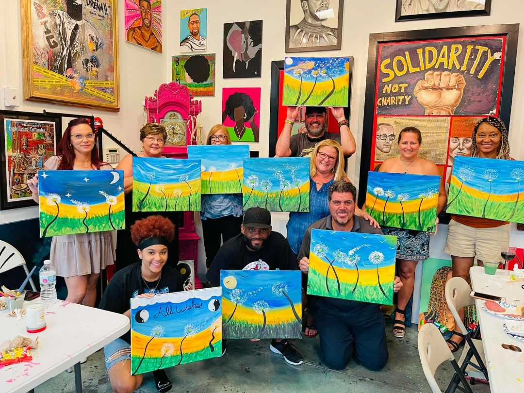 People holding art canvases after an art class.