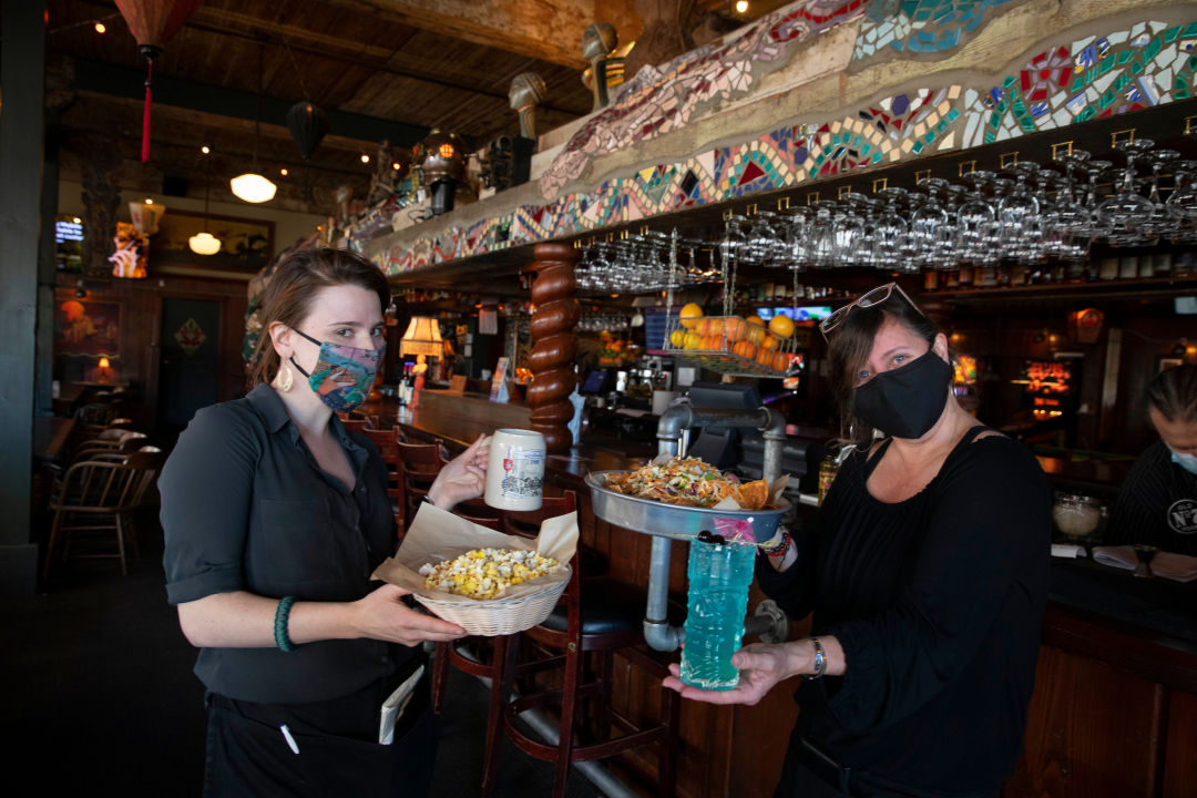 Masked servers at Ringlers holding food and drink items