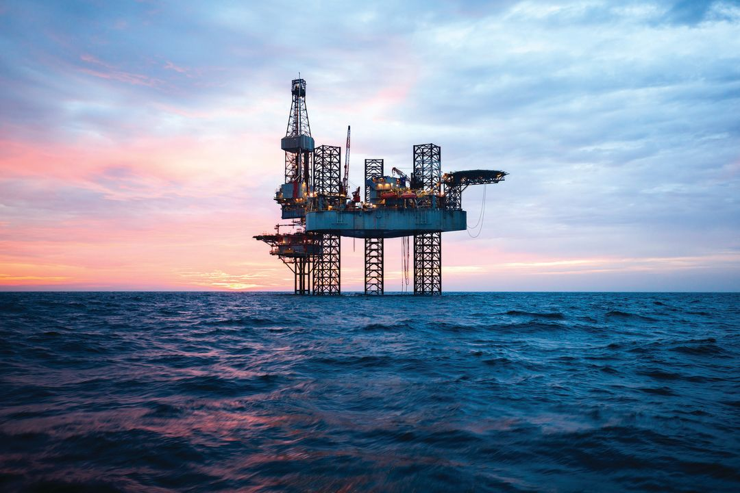 An offshore oil rig stands miles out in the Gulf.