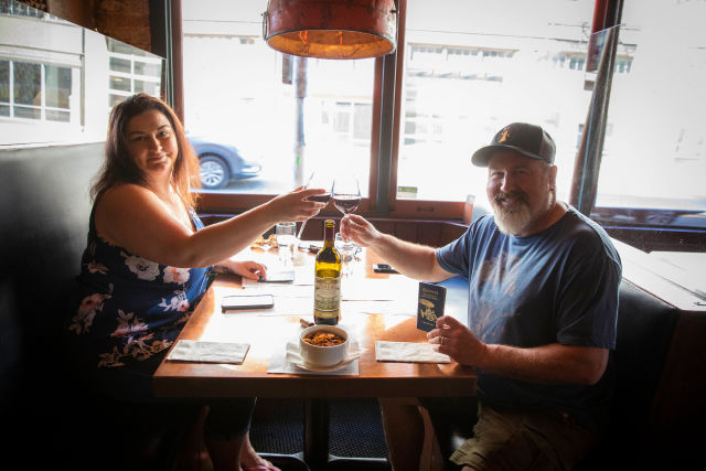 Two people clinking wine glasses at a restaurant table with a McMenamins passport