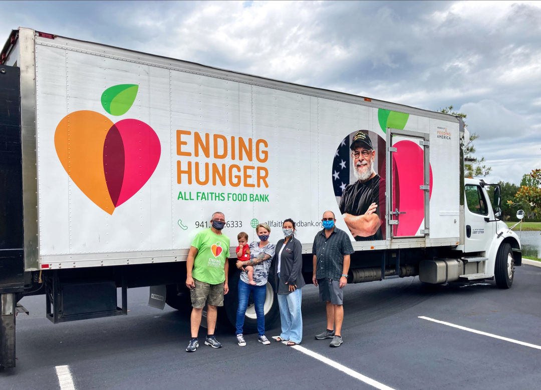 All Faiths Food Bank driver Chad E. (far left) with Safe Children Coalition Youth Prevention Services team members Marlena Calzavara (holding her son), Jen Warwick and Ken Kochenderfer