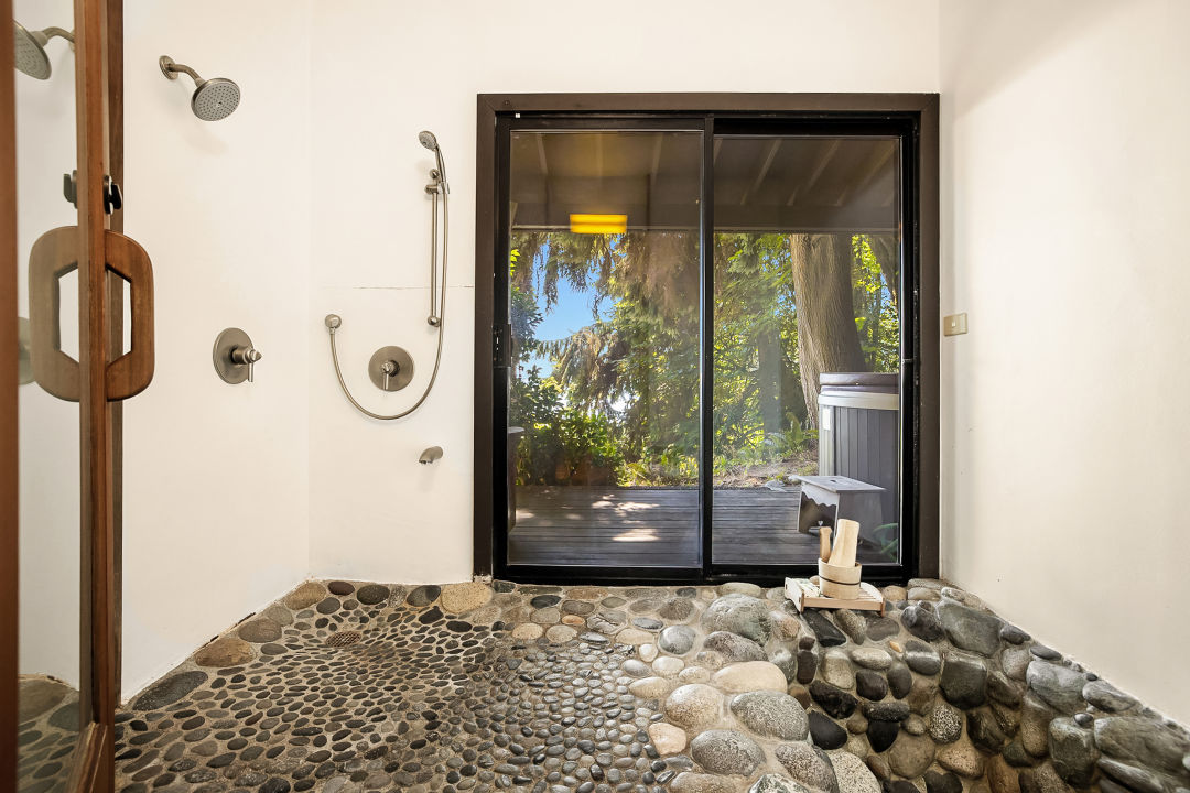 A shower room with white walls and a river-rock floor with recessed bathtub. A glass door on the back leads to a deck with a hot tub, then trees and blue sky.