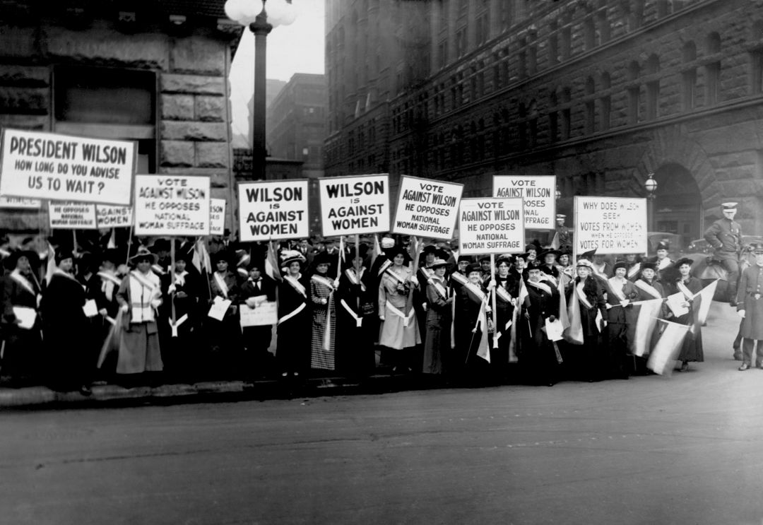 """A crowd of suffragists demonstrate with signs reading """"Wilson Against Women"""" in Chicago in 1916. President Woodrow Wilson withheld his support of suffrage until 1918."""