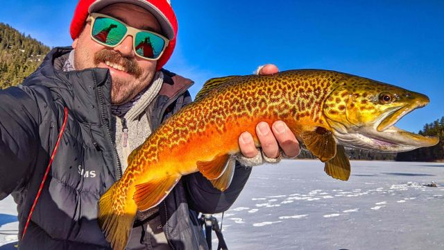 Tyler Hicks and a freshly caught tiger trout on Bonaparte Lake near Tonasket, Washington, just south of the Canadian border
