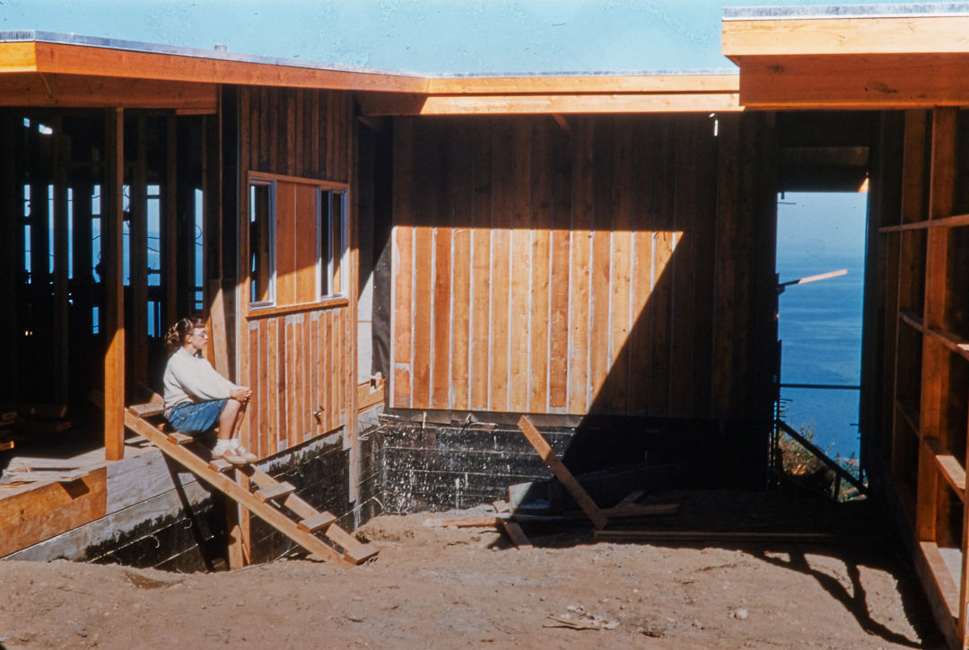 A 1950s photograph of a woman sitting in an unfinished house's timber framing