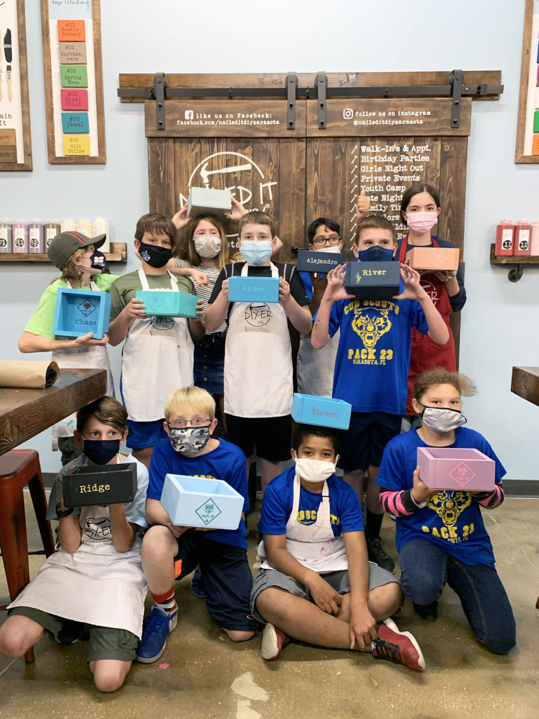 A group of kids at Nailed It DIY studio with their projects