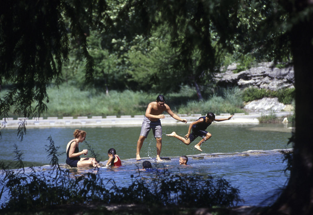 People swim at Falls Dam in Blanco, Texas.