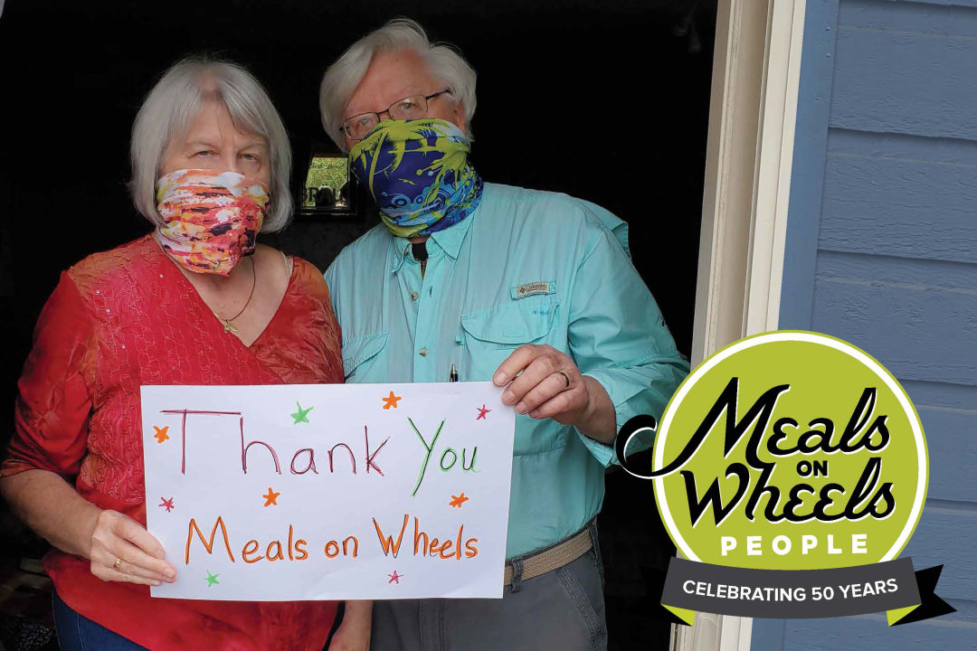 Two people holding up a sign thanking Meals on Wheels People