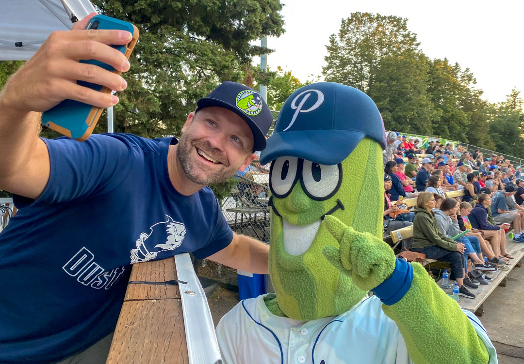 A man poses for a selfie with a person in a smiling pickle costume in the stands at baseball stadium