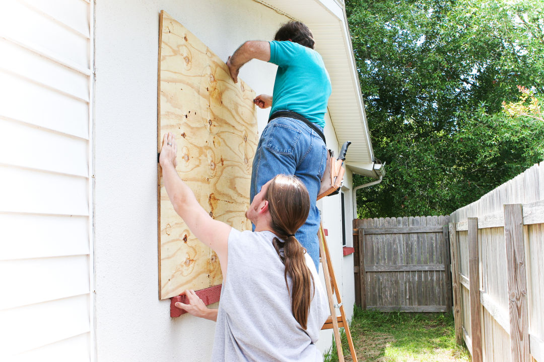 Two people board up a house.