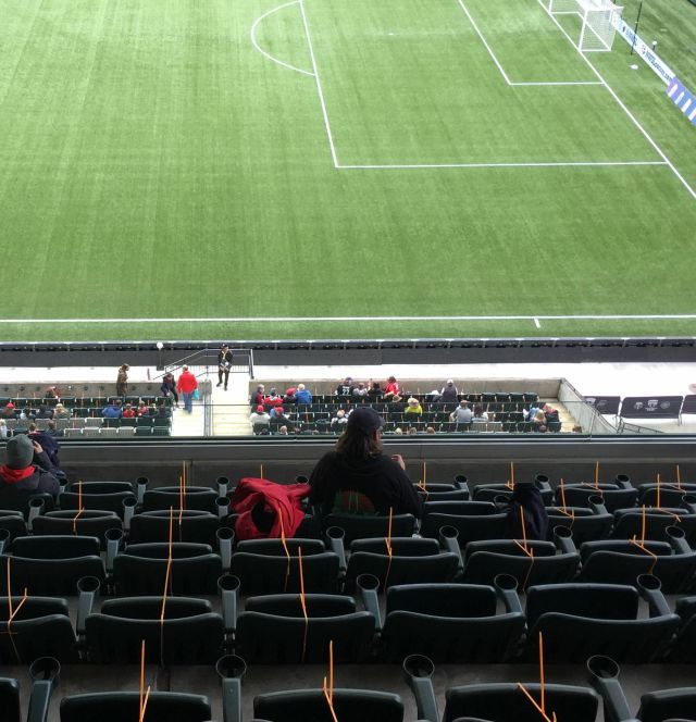Orange zip ties on stadium seats, with the soccer pitch visible below