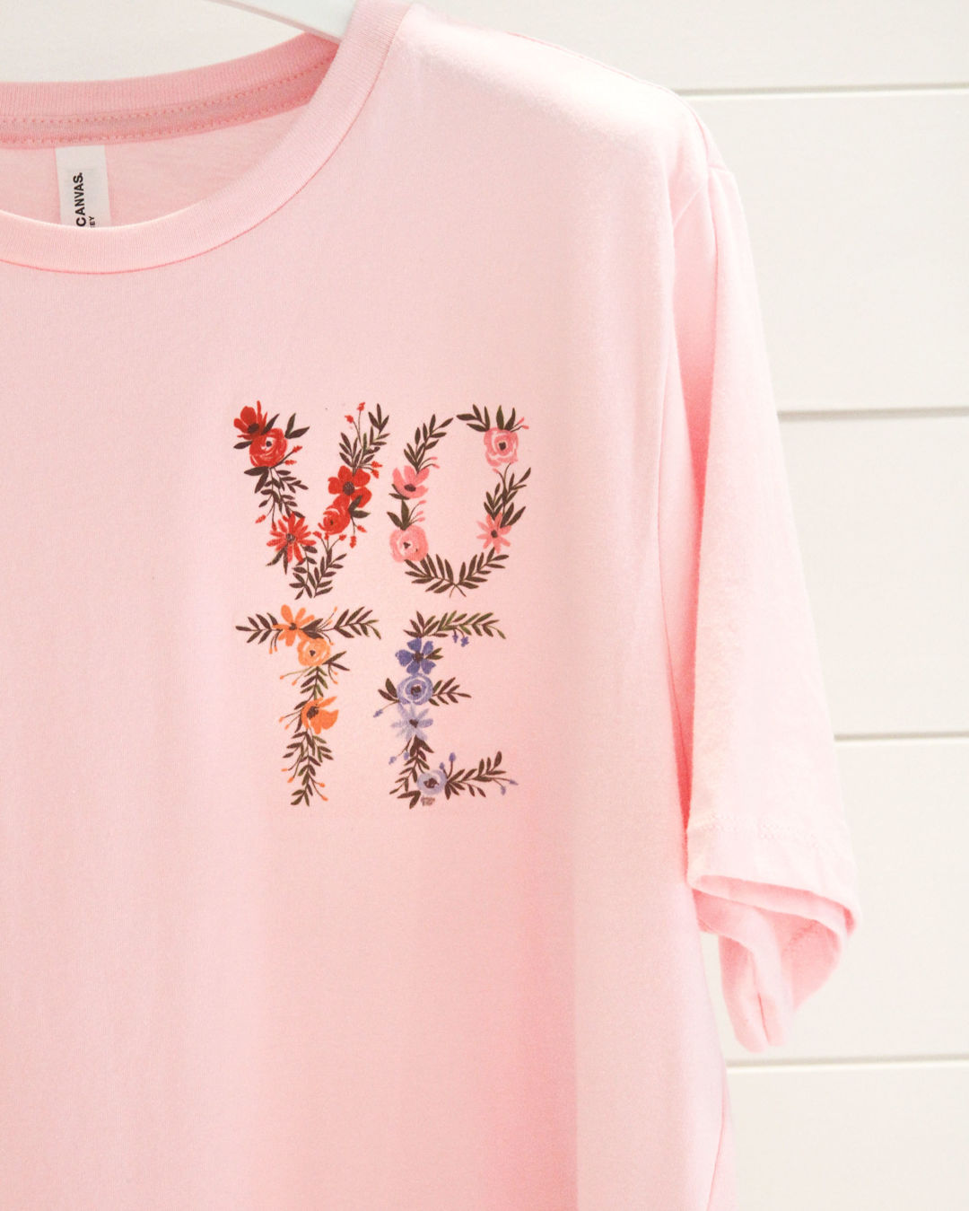 The Camilyn Beth x Shannon Kirsten Vote t-shirt features Kirsten's floral illustration on a light pink tee.