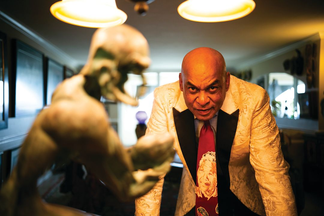 Reggie Williams stands next to one of the pieces in his art collection, a sculpture of a rugby player, in his downtown Sarasota condo.