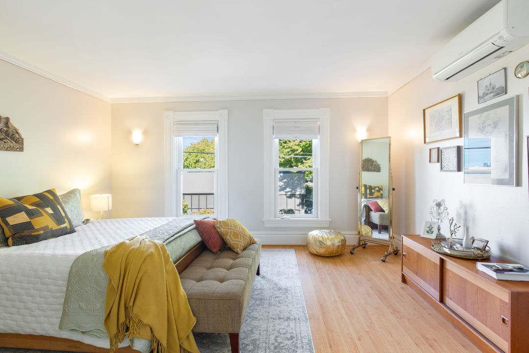 A bedroom with two white-trimmed windows on the far wall, a bed with its head on the left wall, and a low cabinet with framed photos above on the right.