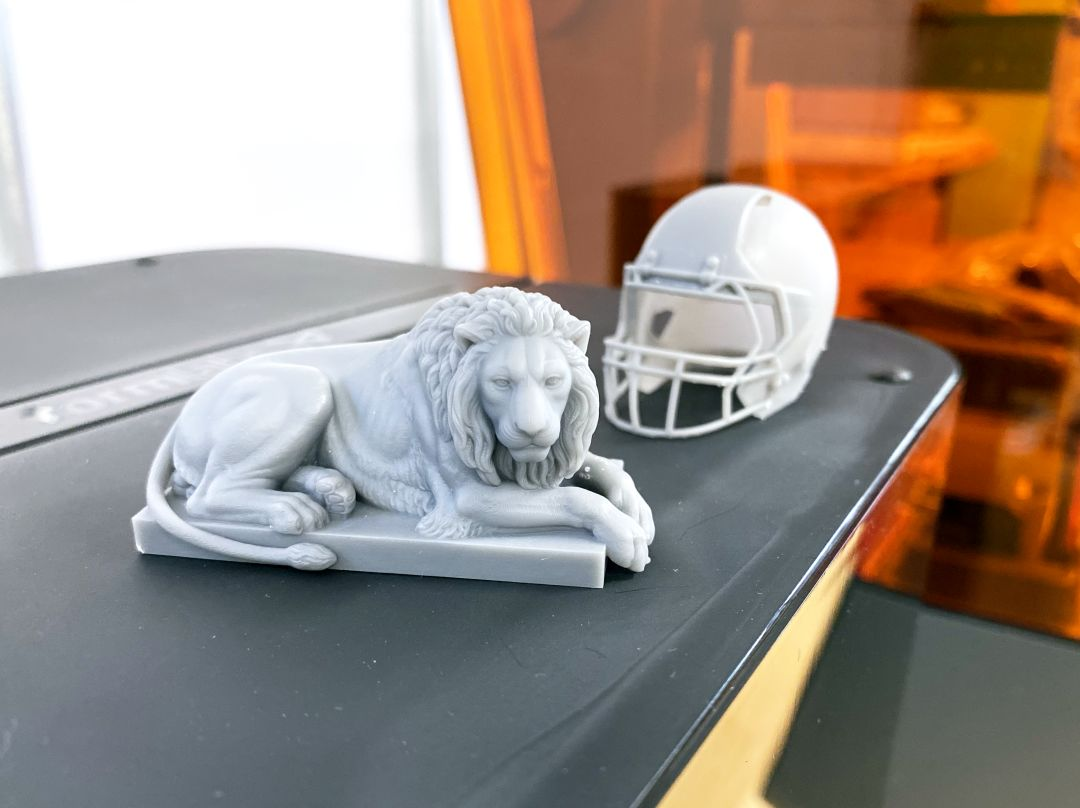 A lion figurine and football helmet printed using the Formlabs Form 3 resin printer show a high level of detail.