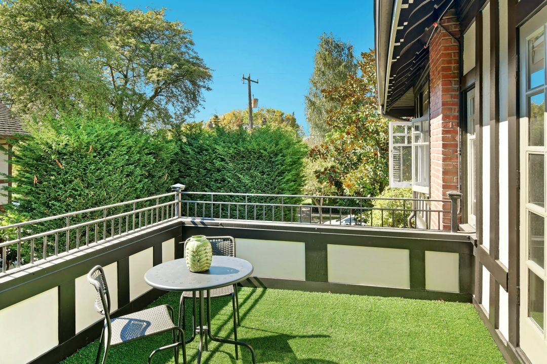 A sunny balcony with a green turf floor and trees in the background.