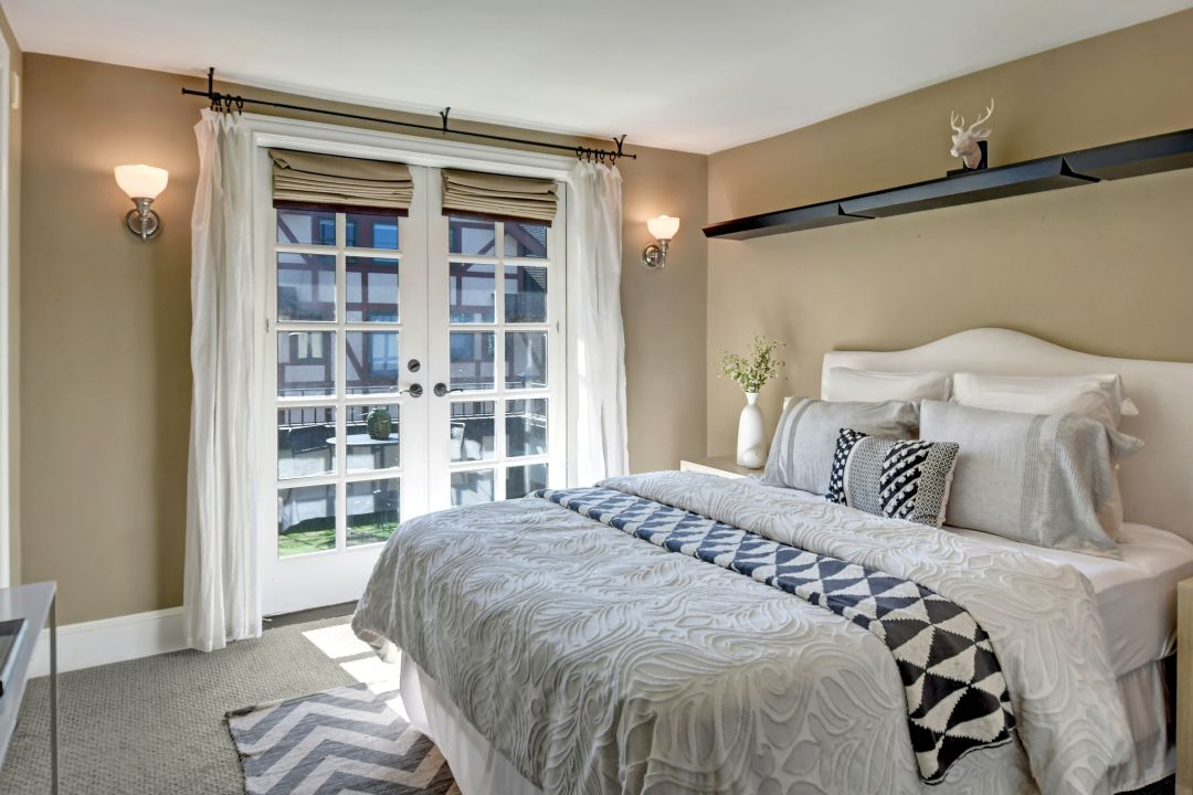 A bedroom with gold walls. On the far wall, white-trimmed French doors open to the outside.
