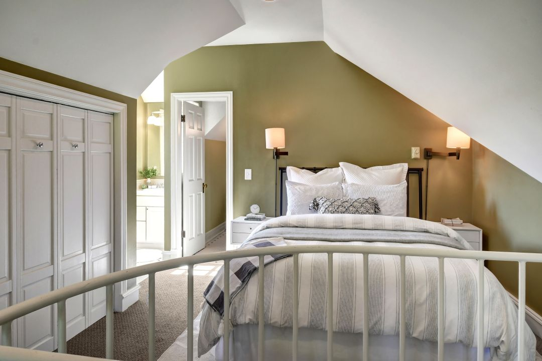 A bedroom with green walls and white trim. A full bed is under a sloping ceiling to the right, and set of built-ins is on the wall to the left.