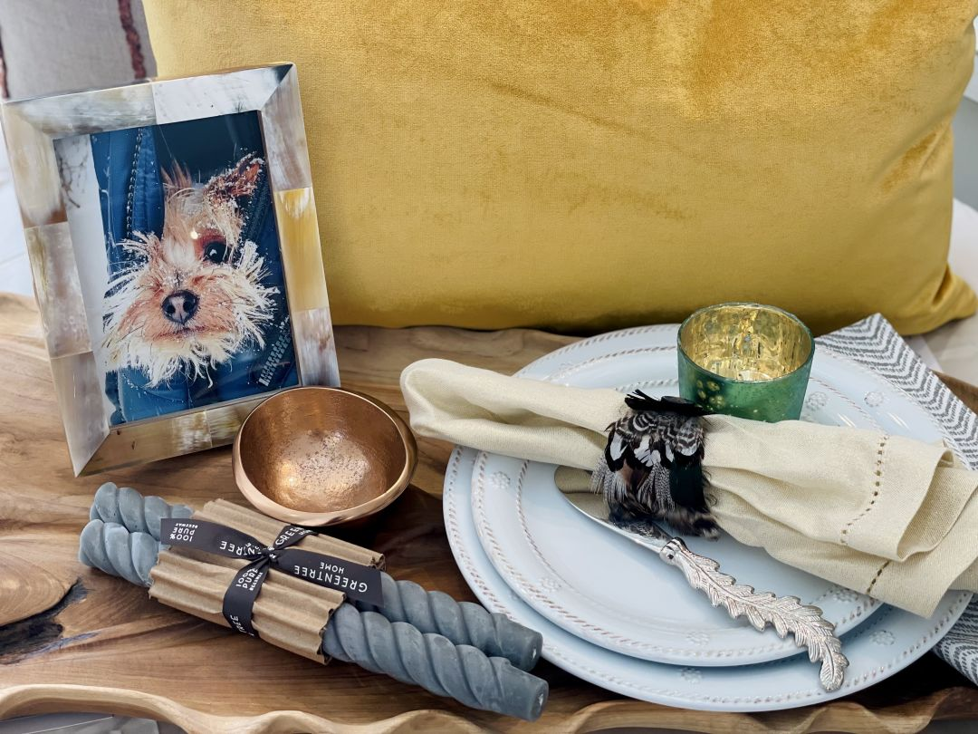 Products include napkin ring, leaf spreader and dishes, rose gold bowl, velvet pillow, tapered candles, wood leaf and picture frame .