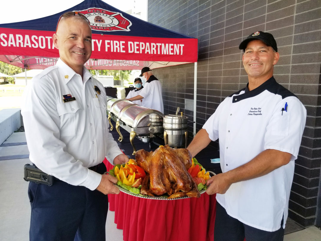 Sarasota County fire chief Michael Regnier with Oaks Club executive chef James Pampinella.