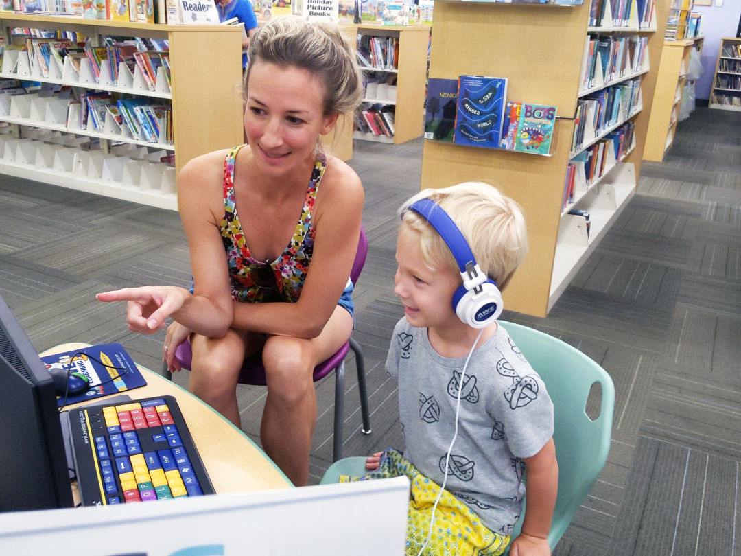 A young family enjoys a new AWE Early Learning Station at Selby Library.