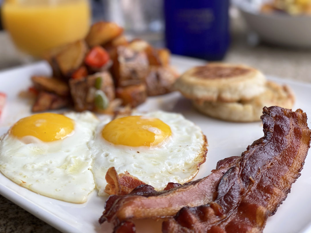 Breakfast plate of sunny side-up eggs, bacon, English muffin, and fried potatoes