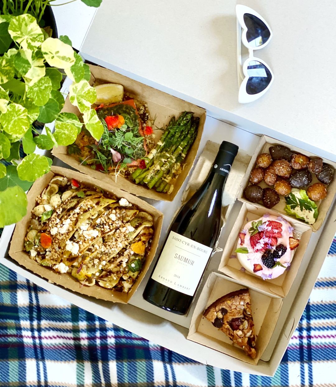 A picnic box full of veggies and wine rests on a plaid blanket.