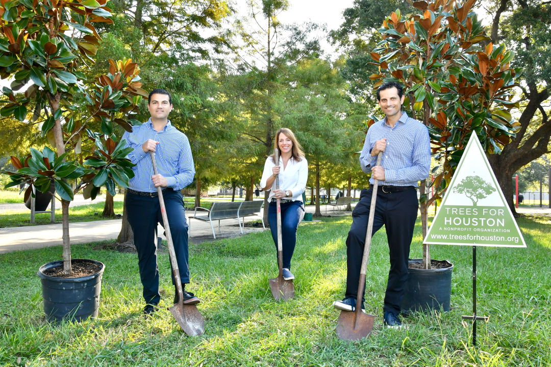 Three people stand with shovels to plant trees.