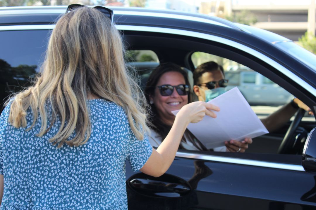 An Adult Leadership Sarasota graduate receives her diploma at the drive-through ceremony.