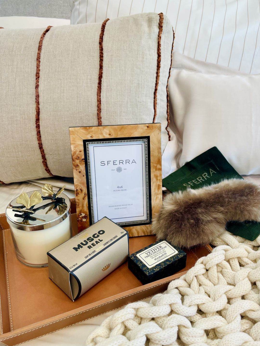A striped throw pillow, knit throw and faux fur eye mask on a leather tray.