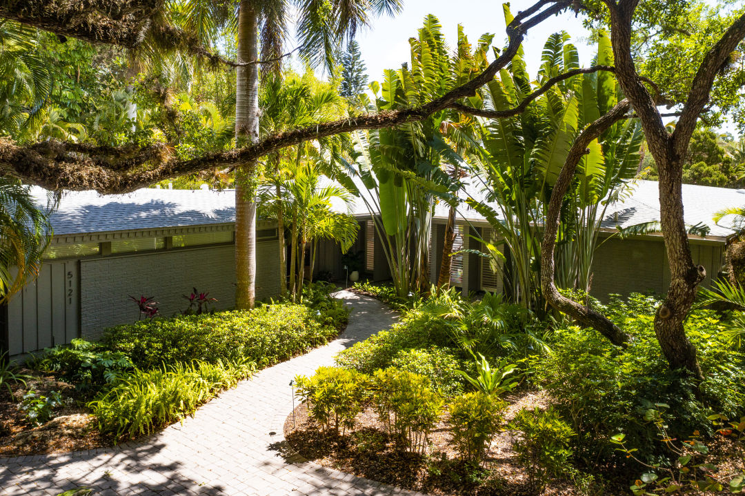 """The home works in harmony with lush landscaping that gives it a """"tucked away"""" feeling."""