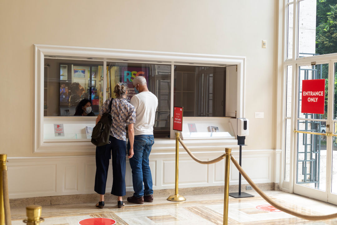 Two people check in at the Portland Art Museum admissions window