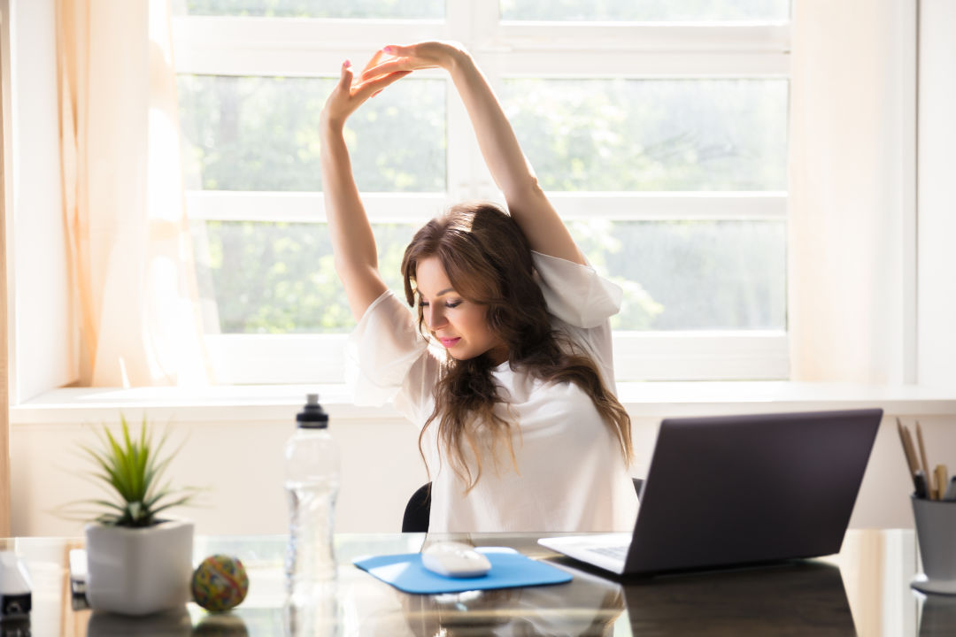 A woman stretches at her desk.