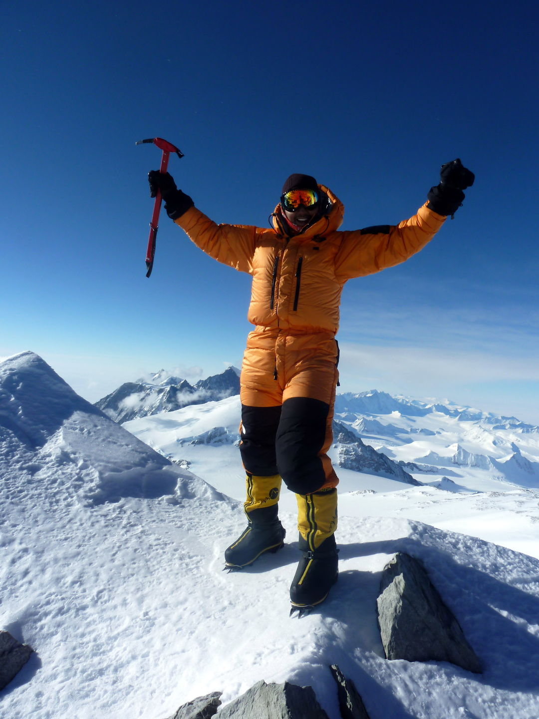 Climber in orange jacket stands on the top of a snowy mountain.