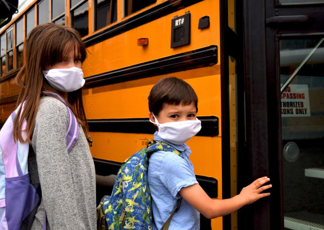 Masked children climb into a school bus.