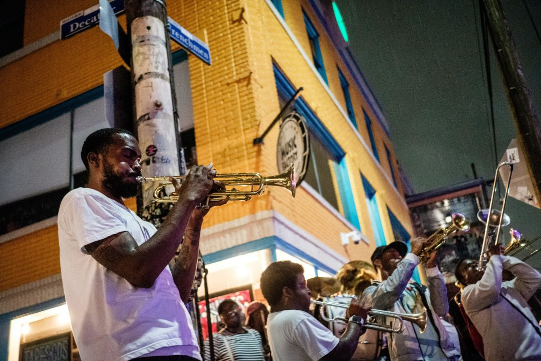 Horn players on a street corner at night