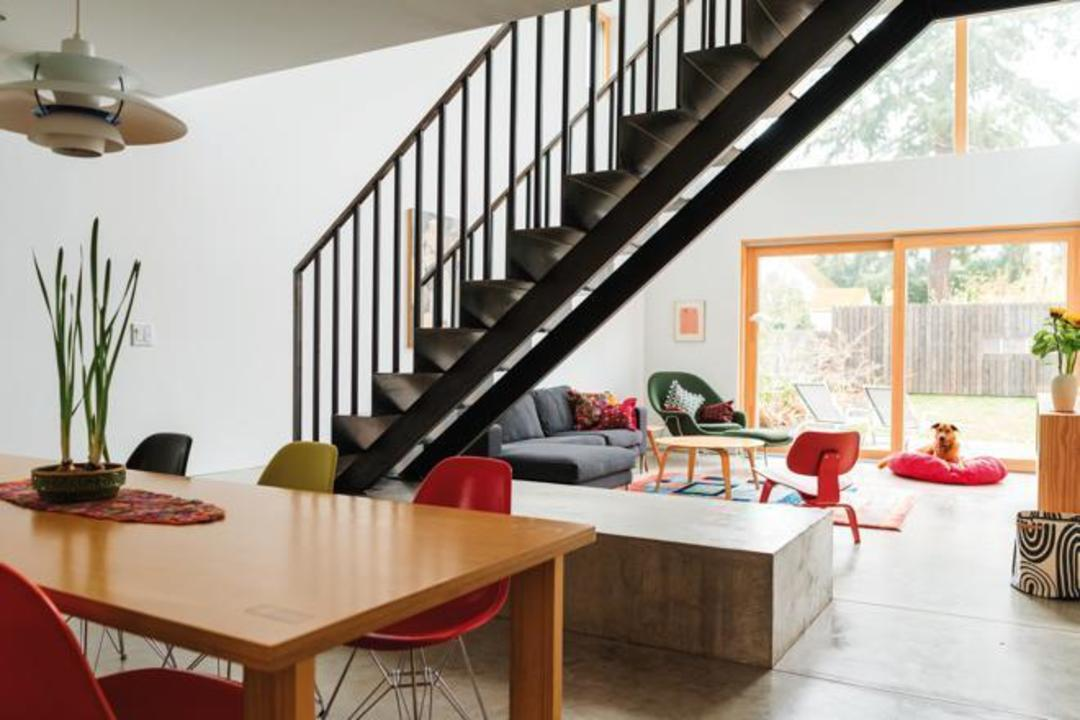 The home is a study in clean design from the folded steel stairs to the midcentury furniture to the exterior below scaled to echo the adjacent houses