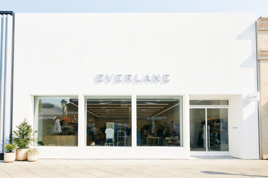 Everlane's storefront at U Village is bright white with large windows and several plants sitting outside.