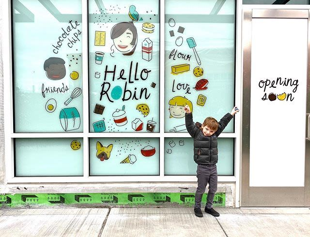 Little boy stands in front of the soon-to-open storefront that says Opening Soon