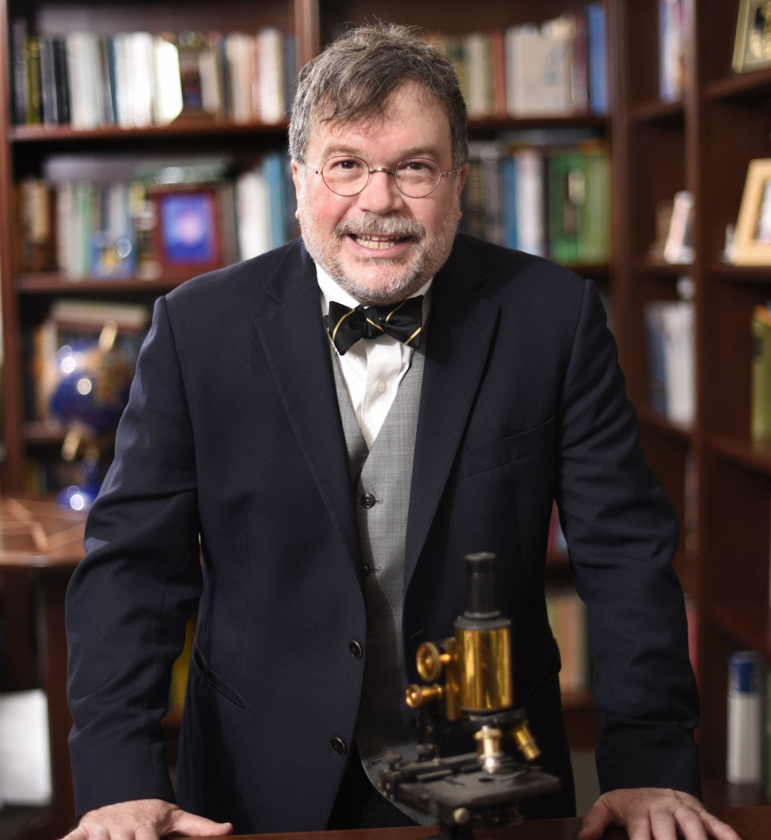 Dr. Peter Hotez stands in front of a microscope.