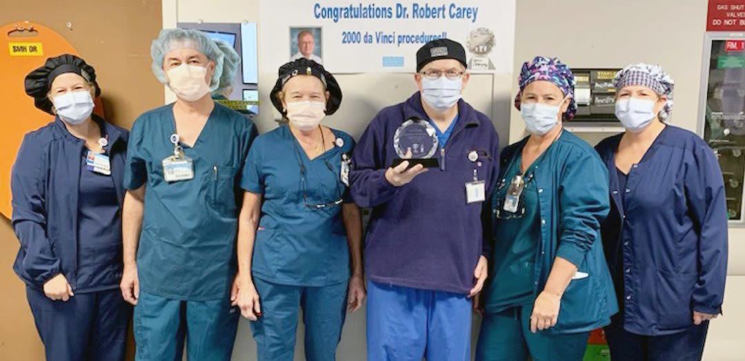 Dr. Robert Carey, center, holding an award for performing more than 2,300 robotic surgeries.