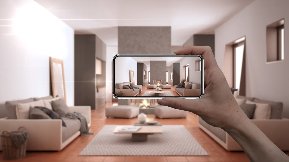 An arm holding up a phone camera that shows the living room of a home