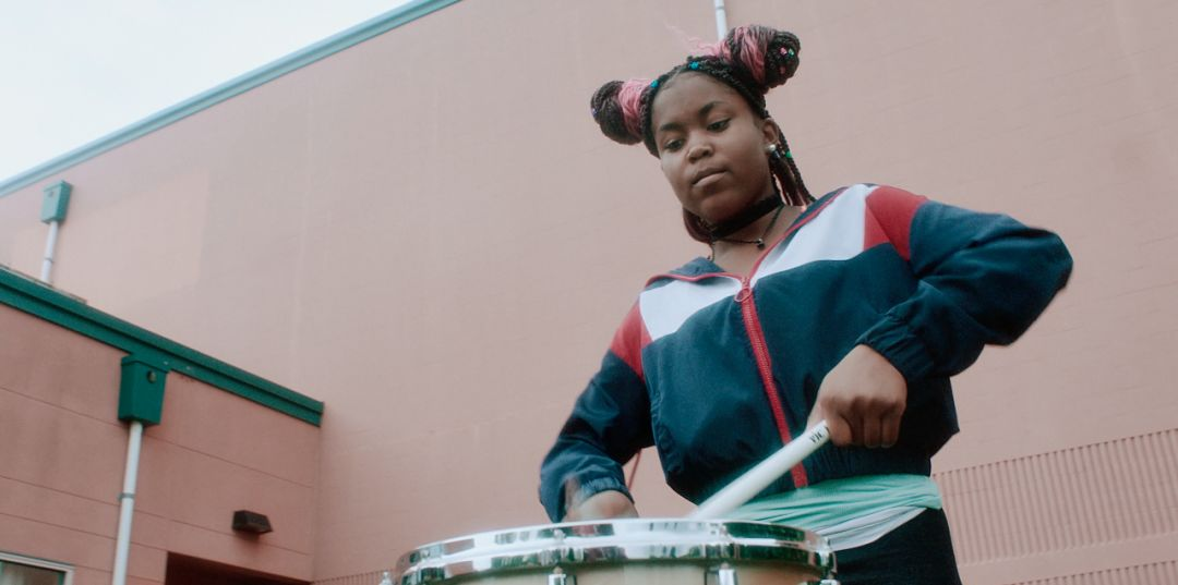 A girl in a blue jacket plays the drum.