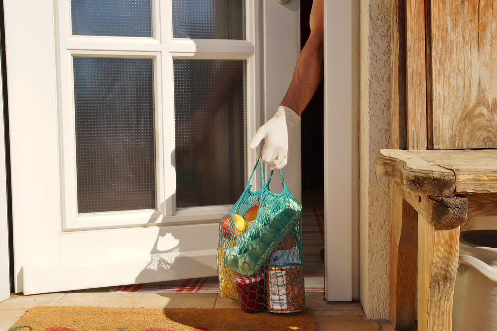 gloved hand picks up groceries left at door