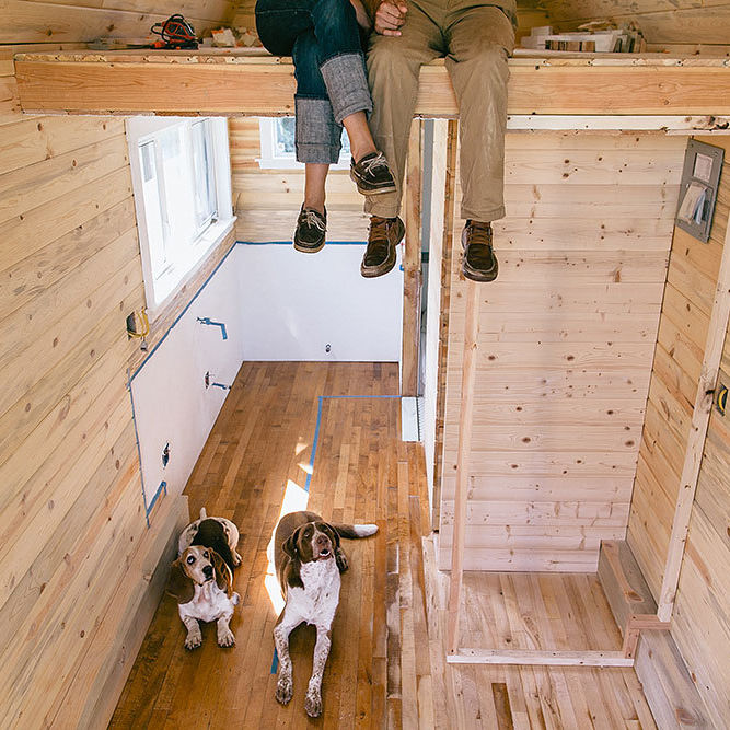 Couple with dog inside tiny house kg2ibj