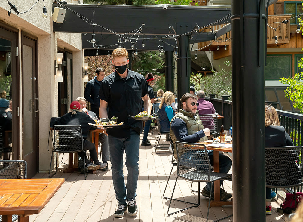 People dine at an outdoor patio while a server wearing a protective mask carries food