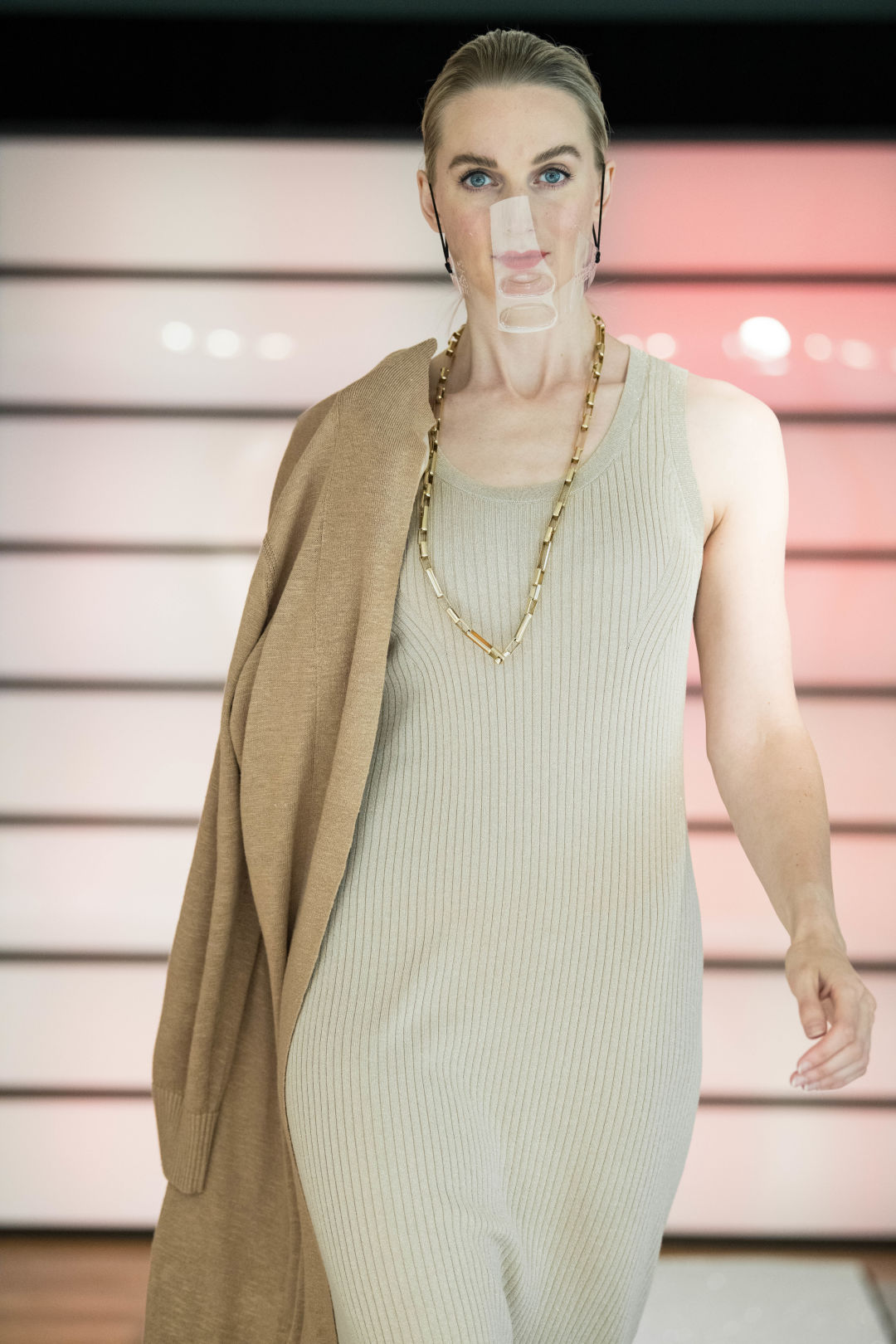 A woman walks a fashion runway in a cream colored dress with a tan sweater draped over one shoulder.