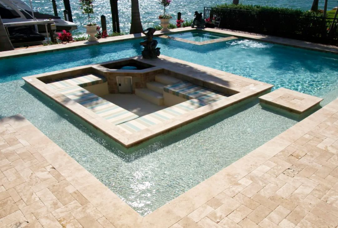 A Freestyle Pool & Spa custom pool with a sun shelf surrounded by a travertine deck area.