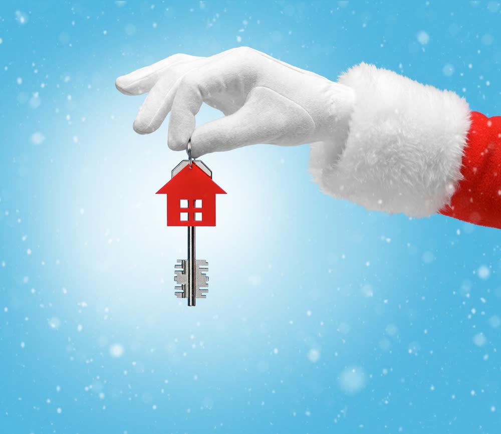 Santa hand holding house ornament with key