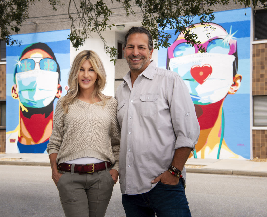 """Donda Mullis and Ronnie Shugar in front of the """"Sarasota Heroes"""" mural at their corporate headquarters on Second Street."""